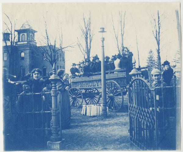 Glee Club students preparing to leave campus in a horse-drawn wagon on College Street, with the old elementary school in the background