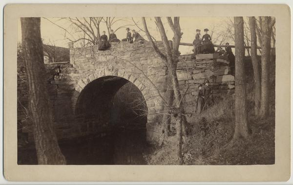 Students sitting on bridge over Stony Brook