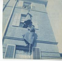 Students practice climbing out of dormitory window down a rope during a fire drill, ca. 1903