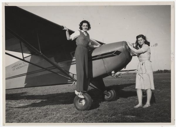 Two members of the Mount Holyoke College Flying Club, l-r, Miriam Bobrow '47 and Ethel Edwards '47, posing with airplane