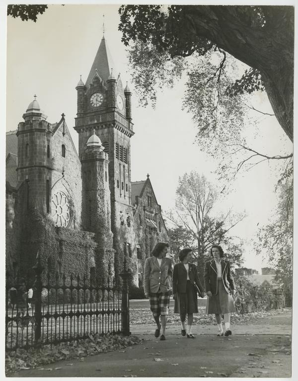 Three students walking north on sidewalk alongside College Street, with Abbey Chapel and Mary Lyon Hall in the background