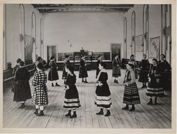 Calisthenics class exercising with Indian clubs, 1876