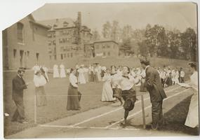 Students running in a track event on Field Day, with Blanchard Gymnasium and Porter Hall in the background