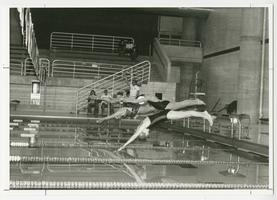Physical education swimming class with students seated on a diving board, watching demonstration of a swimming stroke
