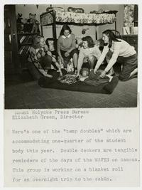 Four Outing Club members in a dormitory room, preparing a blanket roll for an overnight bicycle trip to the cabin