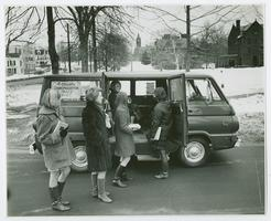 "Students in line at ""4 College Transportation Service"" van on a winter day, with view north up College Street toward Mary Lyon Hall in the distance"