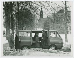 "Students at ""4 College Transportation Service"" van on a winter day, with Mary Lyon Hall in the background"