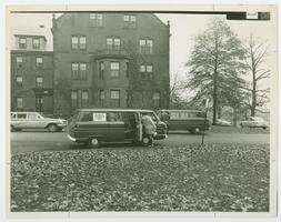4 College Transportation Service van stopping to pick up passengers, with Mead Hall in the background
