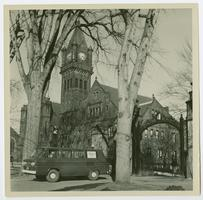 4 College Transportation Service van leaving campus through the main gate of the College, with Mary Lyon Hall in the background