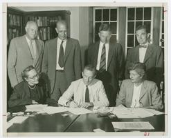 Newton F. McKeon, librarian of Amherst College, signing application for incorporation of Hampshire Inter-Library Center, while fellow librarians Flora B. Ludington of Mount Holyoke and Margaret L. Johnson of Smith look on; in back row, l-r, are presidents