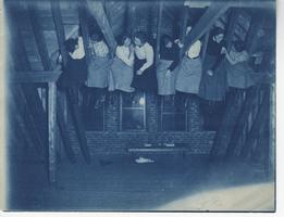 Students enjoy a snack and sit on the rafters in Pearsons Hall attic, ca. 1901