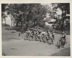 Nine students ride their bicycles through campus past Porter Hall and Mary Lyon's grave, 1942