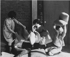Four students enage in a pillow fight, ca. 1960s