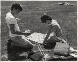 Student and friend prepare a kite for flight, ca. 1960s
