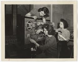 Three students working on equipment in the WMHC radio station
