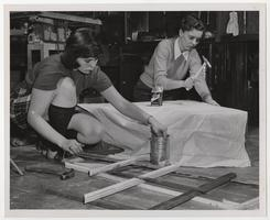 Two members of the Dramatic Club building a set for a play