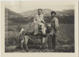 Marion Blake on a donkey led by an unidentified man, with mountains in the background
