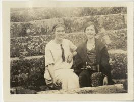 Marion Blake seated on steps (or the cavea of an ancient Roman theater) with unidentified female companion