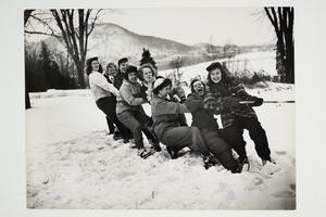 Students tugging a rope in the snow during Winter Carnival, with the Holyoke Range in the background