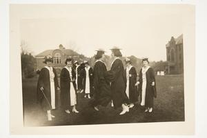 Members of the Class of 1920 participating in Senior Rope Jumping on Skinner Green, with Edith Parker and Marion Ratcliffe in the center and Blanchard Gymnasium and Wilder Hall in the distance