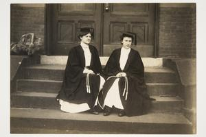 Two students from the Class of 1907 sitting on the steps of Williston Hall, holding their ropes for Senior Jump Roping