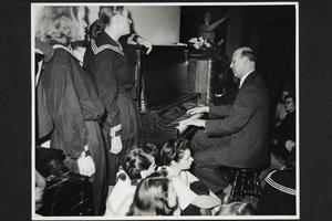 President Roswell Gray Ham playing the piano at the college sing for UN Weekend