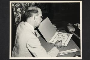 President Roswell Gray Ham signing an illuminated greeting to Princess Juliana of the Netherlands on the occasion of her coronation on September 6, 1948