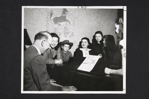 President Roswell Gray Ham at the piano entertaining his undergraduate hostesses after dinner in a dormitory, with his son David looking on