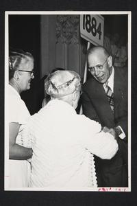 President Roswell Gray Ham shaking hands with two alumnae, l-r, Mary Ruhl '15 and Mary Walker Raymond '84, at a class reunion