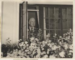 Joseph A. Skinner looks out window, ca. 1940s