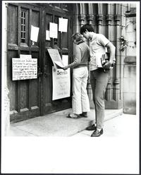 A student and friend reading signs on the library door referring to Mount Holyoke's participation in the nationwide students' strike against the Vietnam War