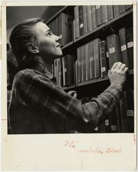 Sarah Young, Class of 1951, browsing in the stacks of Williston Memorial Library