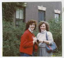 Two students posing for a picture outside a dormitory