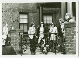 Group of students singing on the porch of Mead Hall dormitory