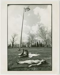 Students relaxing in the spring sunshine near the flagpole