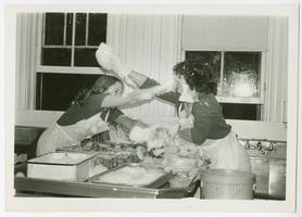 Two students having a soap fight while washing dishes