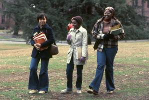 Three students with books walking across campus in the fall