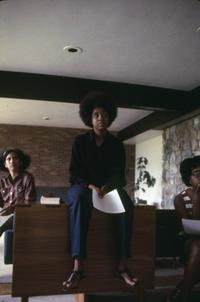 Three students listening at a meeting