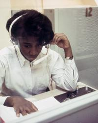 Student operating electronic equipment, wearing headphones