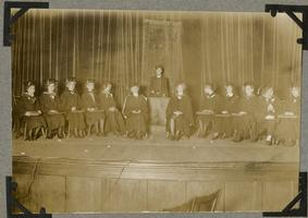Group of students seated on stage, wearing caps and gowns; page from an album of the Class of 1932