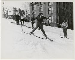 Catharine Warren skiing down the hill between Clapp Laboratory and Pageant Field, with others watching l-r, Ruth Greenwood '51, Abigail Kimball '50, Martha Coachman '52, and Nancy Bird x52