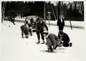 Students putting on snowshoes for a hike to the Outing Club cabin, on Mt. Holyoke
