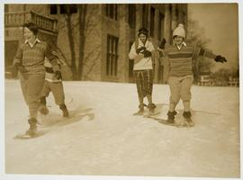 Four students snowshoeing with Clapp Hall in the background