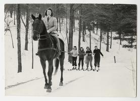Jane Senter '45, on horseback, pulling four other students from Class of 1945 up mountain on skiis