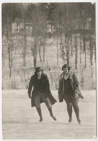 Two students, l-r, Mary P. Bruyn '24 and Winifred A. Sanders x'24, ice skating on Lower Lake with Prospect Hill in the background