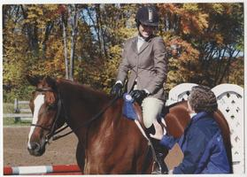 Student on horseback with a blue ribbon, in conversation with C. J. Law, head riding coach