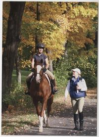 Two students in conversation on a campus riding trail, one on horseback and the other on foot