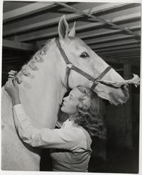 Mary Sherwood Giese '48, braiding the mane of her horse, Grigio