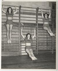Three students exercising on pull-up bars in a gymnastics class