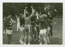 Intramural flag football players cheering, with Anne Kenney '88 in the center, facing outward
